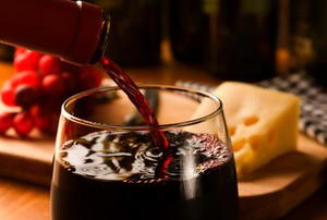wine pouring into a glass with cheese and grapes in the background