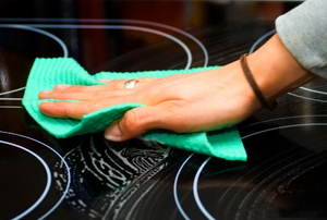 Cleaning a glass cooktop with a turquoise rag.