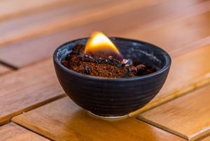 burning coffee grounds in a dish on a wooden table