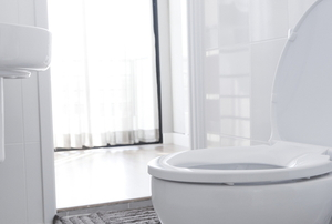 A toilet in a bathroom with bright light and white surfaces