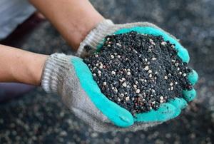 gloved hands full of soil
