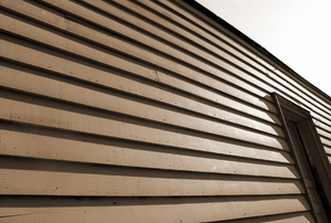 A side of a house with wood siding.