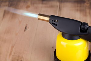 A yellow soldering torch with a flame.