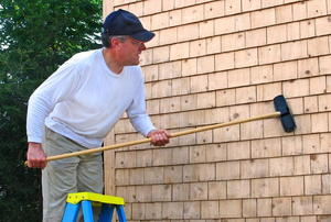 A man working on wood siding with a broom.