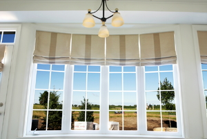 A set of brown roman shades fitted to tall windows.