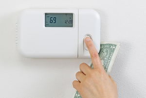 A hand adjusting a digital thermostat while holding cash.