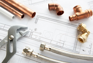 Copper joints, pipes and other supplies laying on blueprints