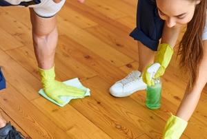 two people polishing a wood floor