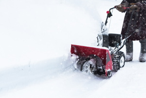 A man pushes a snowblower.