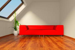 Light shining through a skylight onto a red couch in a finished attic.