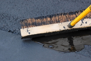 a brush pushing driveway sealant