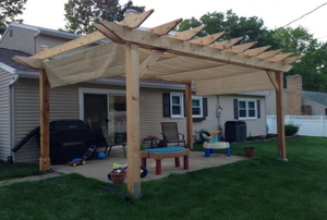 a pergola on top of a  concrete porch with a lawn surrounding it