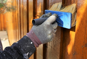 brushing stain onto a wood fence
