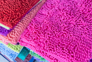 A stack of colorful shag rugs.