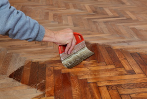 A man applying finish to a wood floor.