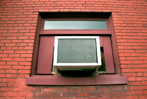 A window air conditioner outside of a brick building.