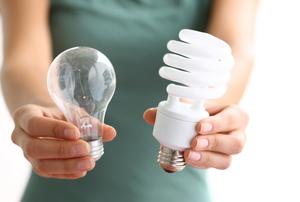 person holding two types of light bulbs