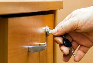 Hand unlocking a drawer