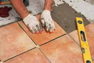 worker with gloves laying down tiles