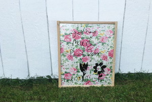 A dry erase board made with glass and floral paper in a frame.