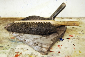 Dirtied linoleum floors with a broom and dustpan sitting on top.