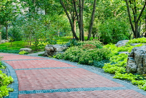 red paver walkway on a slight slope surrounded by greenery