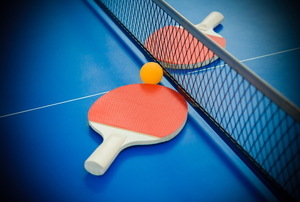 A blue ping pong table with a net and two ping pong paddles.