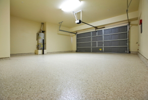 An empty garage with a painted concrete floor.