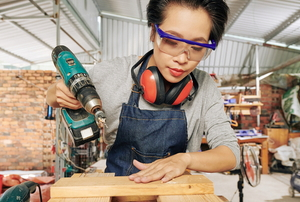 woman building wooden shelf