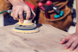 woman sanding a wooden surface with an electric power sander