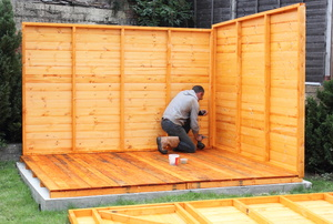 A man working on a shed base.