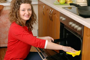 A woman cleaning the inside of her oven with a rag.