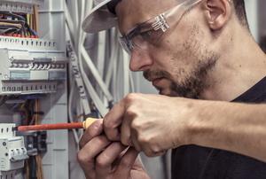 man screwing wire into circuit breaker