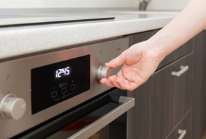 person turning knob to change temperature on stainless-steel electric oven