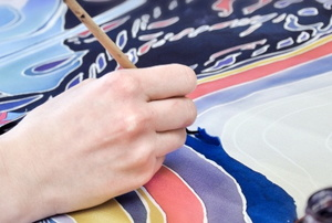 hand drawing an elegant colorful design on fabric