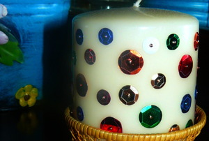 A crafter's sequined, white pillar candle.