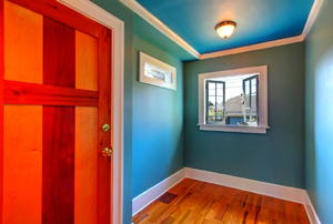 A robin's-egg-blue room with white baseboards and crown molding, as well as a wooden door and floor.