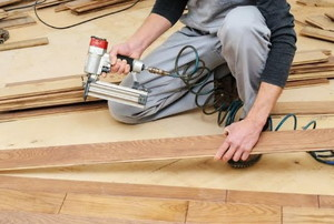 a man installing wooden flooring