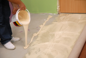 Carpet glue being poured on a concrete floor.