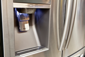 A water and ice dispenser in the door of a stainless steel refrigerator.