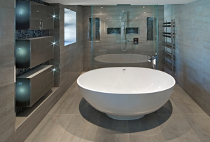 A white oval shaped bath tub in an expensive new home in an ultra modern bathroom.