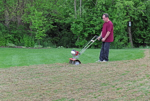 A man using a power rake to dethatch a lawn.