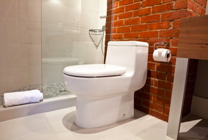 White toilet in a bathroom with a brick wall