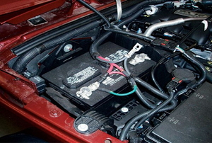 A battery connected inside of a red vehicle.