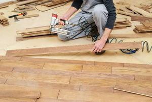 A man installs vinyl plank flooring.