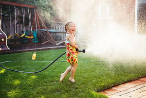 A girl holding a hose that's spraying water all over a lawn in a backyard.