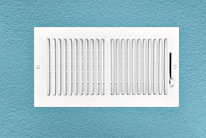 A white air vent on a blue wall.