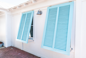 White house with two light blue Bahama shutters