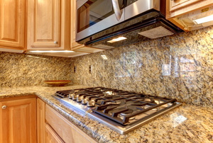 An over-the-range microwave in a granite kitchen.