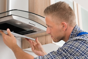 Man removing screen from over-the-range extractor fan